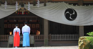 Japanese couple wearing traditional Japanese clothes in front of a shrine